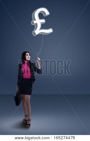 Young businesswoman holding currency symbol of pound sterling