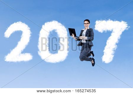 Young businesswoman jumping on the sky while holding a laptop with clouds shaped number 2017
