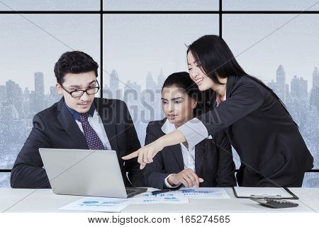 Portrait of female entrepreneur showing business document on the laptop to her partners