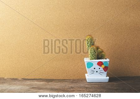 cactus in ceramic pot on wooden table with Vintage brown paper Background Texture.
