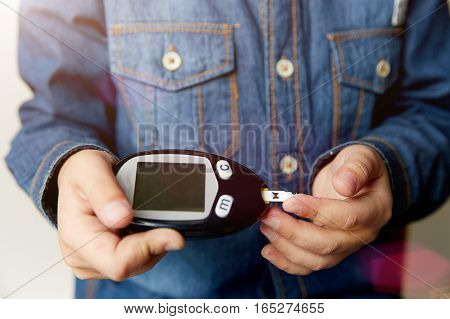 A boy hand holding Glucometer for Blood Glucose Testing on wood table, Healthcare and Medical Glucometer Technology background concept