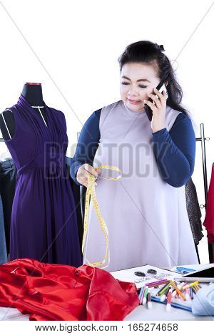 Female fashion designer looks busy talking on the mobile phone while holding a measuring tape