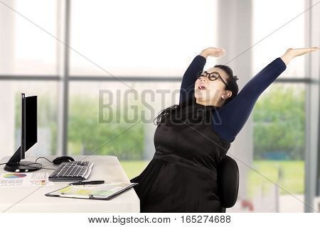 Picture of a cheerful businesswoman expressing her victory by raising hands with financial graph and computer on the table in the office
