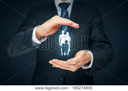 Family life insurance, family services and supporting families concepts. Businessman with protective gesture and silhouette representing young insured family. Central composition.