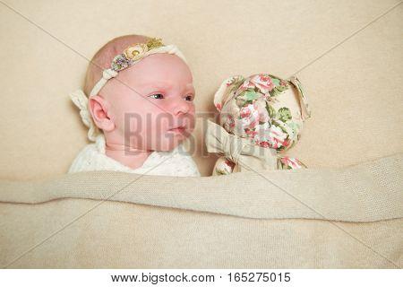 Newborn baby and Teddy bear lying on brown blanket