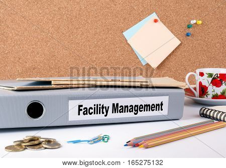 Facility Management. Folder on office desk. Money, Coffee Mug and colored pencils