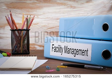 Facility Management, Office Binder on Wooden Desk. On the table colored pencils, pen, notebook paper.