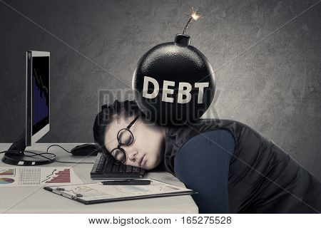 Young entrepreneur feels tired with a bomb of debt over her head while sleeps on the keyboard