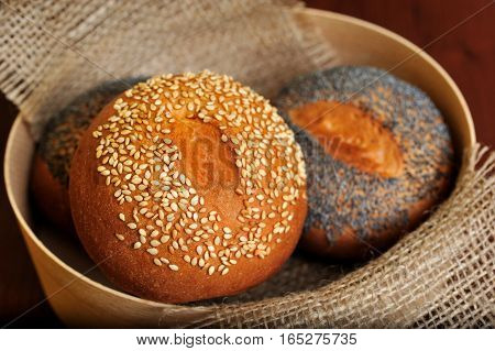 still life focused on bun with sesame seeds in basket with burlap