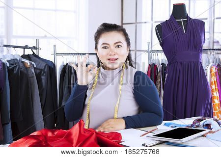 Beautiful Asian fashion designer showing OK sign while working in the office with clothes hanger on the background
