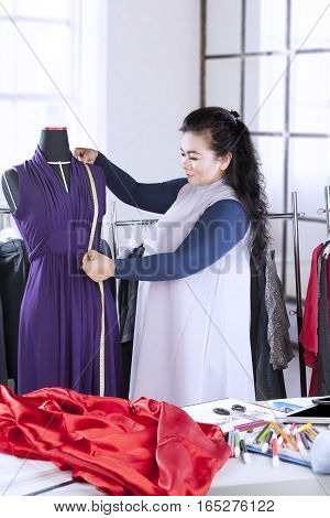 Portrait of a young female fashion designer measuring a dress on the mannequin with a measuring tape at workplace
