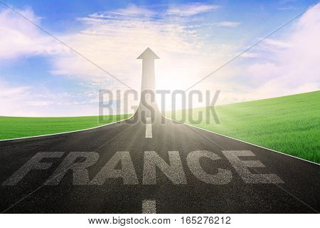 Image of France written on the asphalt road with arrow upward at the end of a road