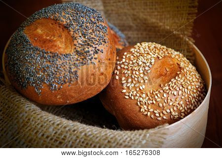 buns with sesame and poppy seeds in burlap basket