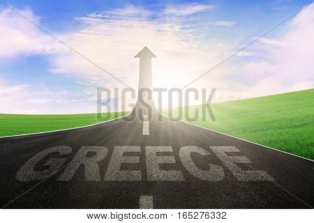 Empty road leading to an arrow upward and symbolizing success with a word of Greece on the street