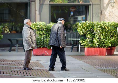 BERGAMO, ITALY - DECEMBER 2016: Two seniors walking at street of Bergamo town, Italy