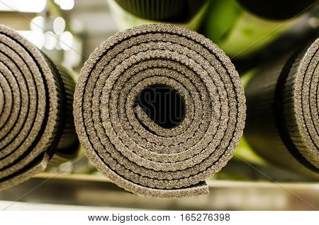 Rolled new yoga mat on a shelf in a supermarket store. Shallow depth of field.