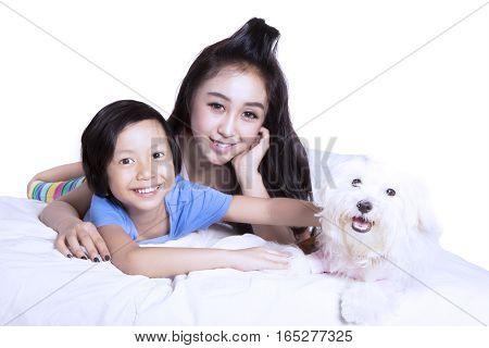 Image of cheerful little girl and her mother looking at the camera and lying on the bed with their puppy