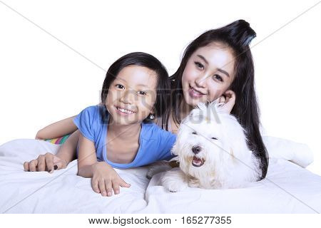 Portrait of young beautiful mother and her daughter embracing their puppy while lying on the blanket