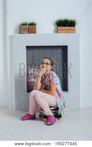 Clever girl schoolgirl sitting with book. The concept of childhood and education.