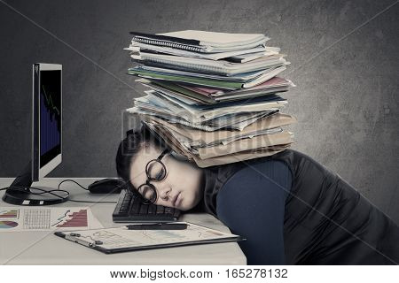 Stressful businesswoman sleeping on the keyboard with pile of documents over her head