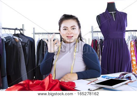 Photo of a successful female fashion designer showing OK sign with clothes hanger on the background