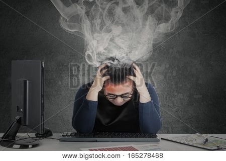 Picture of young woman feeling dizzy with financial chart on desk while smoke coming out of her head