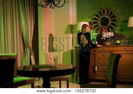 Beautiful young woman in a luxurious classic interior. Elegant young woman posing in vintage interior. Fashion shot. Fashion art photo. Light colored spotlights. Fashion concept. Blond woman