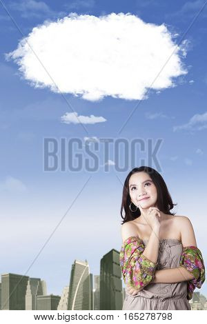 Portrait of young woman daydreaming with bubble cloud while standing under cloud