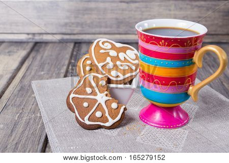 Coffee with homemade gingerbread on tissue and the grey wooden table. Copy space