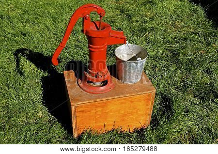 A mounted hand pump on a box with the capabilities of filling a metal pail.