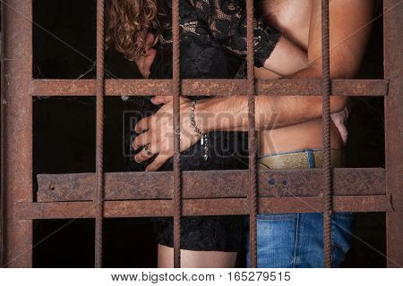 Loving young couple hugging behind bars man and woman are cuddle together