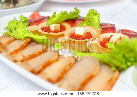 tartlet with red salmon caviar with butter on a festive table near the sausage meats and green lettuce on a light background