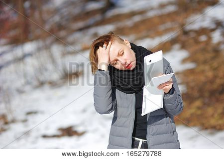 Portrait of young attractive girl in a grey jacket looking at the screen of a modern smartphone in a snowy Park on a Sunny day