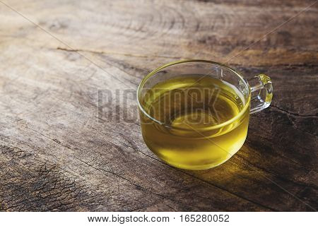 cup of chamomile tea with chamomile flowers on wooden planks on vintage tone