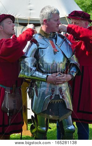 SAFFRON WALDEN, ESSEX, ENGLAND - JUNE 05, 2016: Man being dressed in Elizabethan armor by men in costume.
