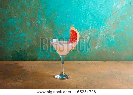 Cocktail with slices of grapefruit on a turquoise background. Grapefruit Martini . Copyspace