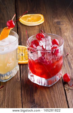 Cocktail cherries with ice on a wooden background