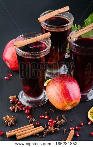 Mulled wine with cinnamon and spices on a dark background