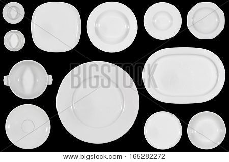 Variety of white plates of different sizes and shapes on black background directly from above