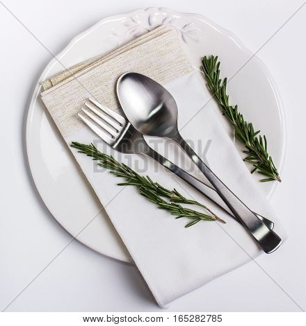 Beautiful Plate spoon and fork on a napkin with rosemary for decoration. Beautiful dishware traditional style.