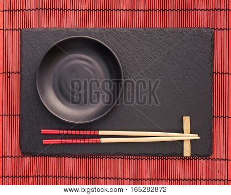 Chopsticks  and black plate  on slate coaster on red bamboo scroll mat. Japanese style food background.  Top view with copy space