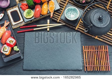 Japanese style tableware with sushi set and tea  on black table,  top view