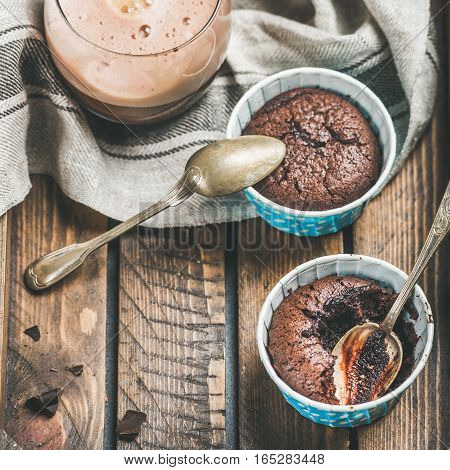 Chocolate souffle in individual baking cups and chocolate mocha coffee in wooden serving tray, top view, copy space, square crop, selective focus