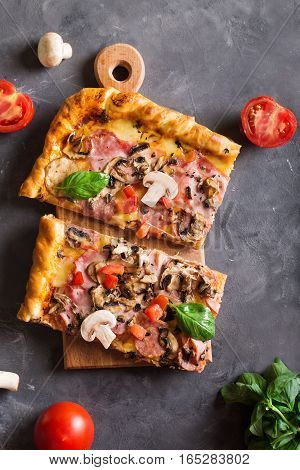 slice of square pizza with basil tomatoes and mushrooms on a wooden board. Top view. Copyspace. Pizza on the gray table