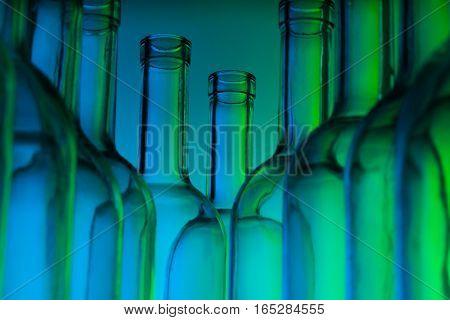 Bottlenecks of empty glass wine bottles on green background
