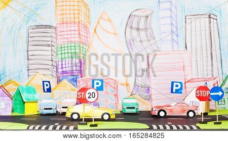 Picture of road traffic at the toy city with signs, paper houses and cars models