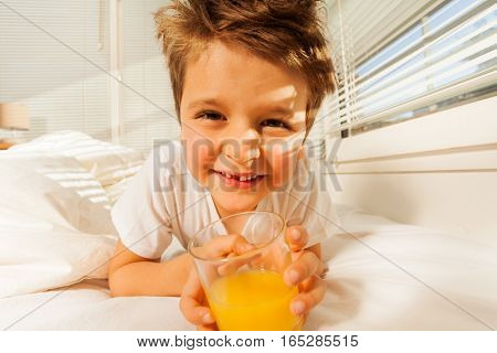 Close-up portrait of happy boy laying in bed with glass of fresh orange juice in his bedroom