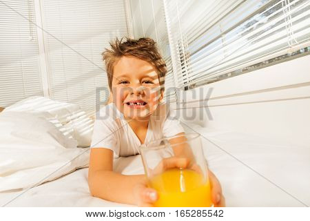 Portrait of happy boy laying in bed with glass of fresh orange juice in sunny morning