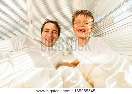 Portrait of happy father and his kid boy awakening in their bed in sunny morning