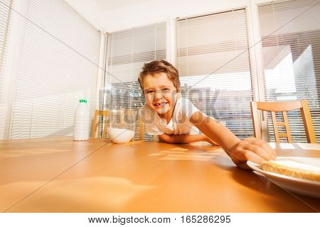 Portrait of smiling kid boy making a long arm for plate with sandwich, sitting at a table in the kitchen